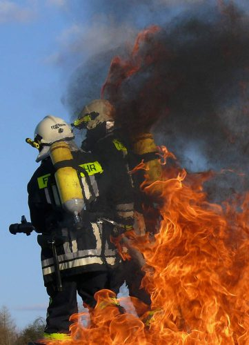 Zwei Feuerwehrmänner der Freiwilligen Feuerwehr Hausen löschen im Rahmen ihrer Mitgliedschaft im Verein einen Brand.